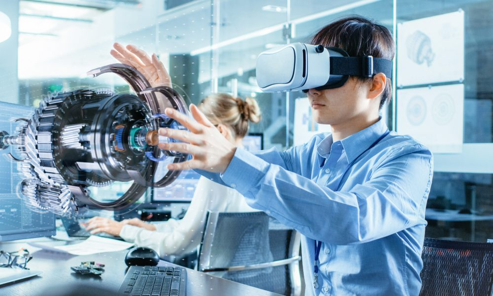 Computer Science Engineer wearing Virtual Reality Headset Works with 3D Model Hologram Visualization, Makes Gestures. In the Background Engineering Bureau with Busy Coworkers.